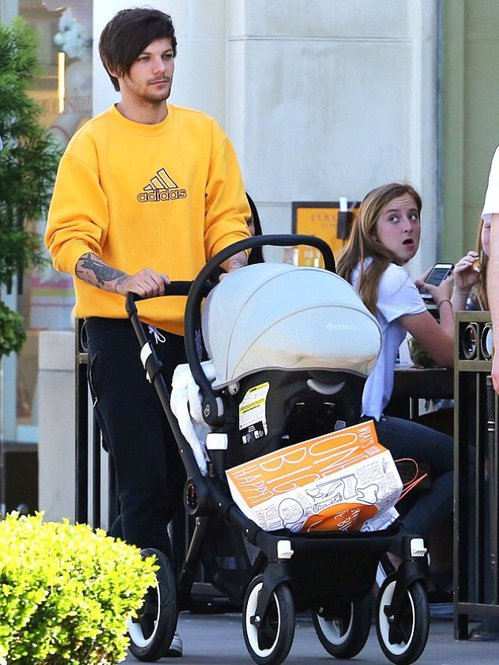 ZOMG that IS Louis Tomlinson of One Direction pushing his kid Freddie or whatever in a Bugaboo Buffalo stroller with a Maxi-Cosi Mico Infant Carrier and appropriate adapters, each sold separately, how ever did this picture happen, what with his body guard on one side and his posse member/paid friend on the other, the mind reels but the pap experts at x-online know how these things are done.